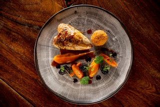 Roast crown of Braithwaite Moor partridge with confit leg bon bon, sweet potato, liquorice infused blackberries and bee pollen
